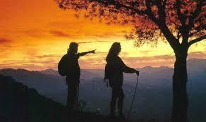 Un grupo de senderistas viendo una puesta de sol mientras practican senderismo nocturno por la Sierra de Guadarrama.