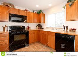 brown kitchen cabinets with black appliances stock photography