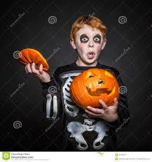 Kids Skeleton Halloween Costume by Surprised Red Hair Kid In Halloween Costume Holding A Orange