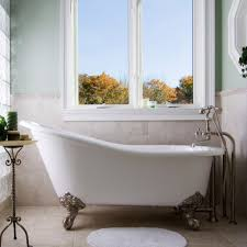 glass windows with small bathroom mat and classic clawfoot tub