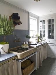 french country kitchen uses cabinet curtains instead of wood doors