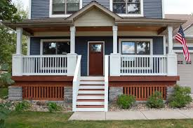 white concrete porch with black metal railing plus beige wall