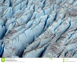 closer aerial view of icy blue color crevasse of glacier stock