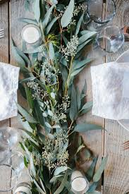 table centerpiece with seeded eucalyptus and candles party ideas