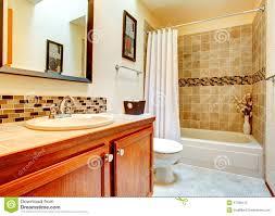 bathroom interior with beige tile wall trim white bath tub with