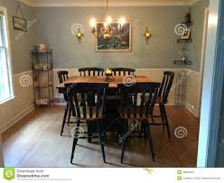 dining room with bar height table and original oil painting