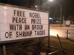 "Sign outside a restaurant that says ""Free Nobel Prize with every order of shrimp tacos"""