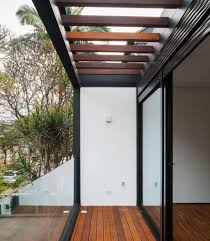 wooden pergola and sliding glass panel also dark steel trusses