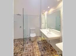 bathroom frameless glass high ceilings tile floor travertine