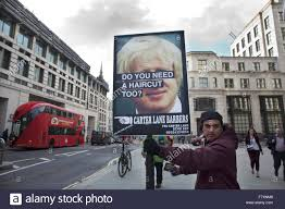 man holding placard advertising haircuts with reference to boris
