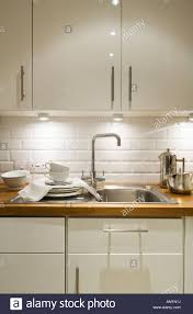 Detail Of Kitchen Sink And Cupboards With Running Bond White Tiles - Kitchen sink cupboards