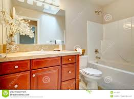 beautiful bright bathroom with cherry wood cabinets stock image