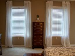 traditional bedroom with short window long curtains and white