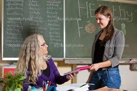 Student giving her teacher the homework she made earlier    Photo by Fotosmurf Depositphotos