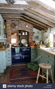 blue aga set in brick recess in cottage kitchen with pale gray