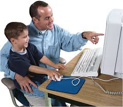 child being helped by father in front of a computer