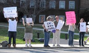 Theoretical Perspectives on Social Stratification    Sociology philschatz com A group of people are shown standing on a sidewalk holding protest signs