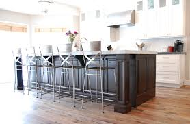 a transitional white kitchen with a dark cherry wood island