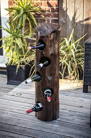 dirty old tree trunk is transformed into a rustic diy wine rack