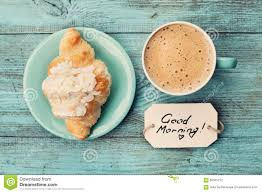 coffee mug with croissant and notes good morning on turquoise