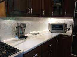fashionable white glass tile backsplash with black kitchen island