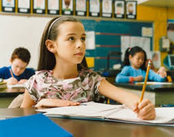 Young Girl Writing in Her Exercise Book in the Classroom At school