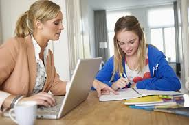 Mother helping daughter with homework at dining room table Verywell