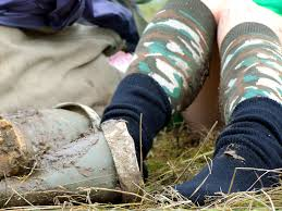 A woman     s legs with army print socks and green wellies