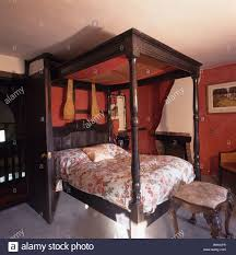 antique fourposter bed with floral bedlinen in red country bedroom