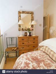 Pine Drawers Floral Mirror Above Pine Chest Of Drawers With White Lamps In