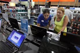 An employee helps a customer shop for a computer at an electronics store in Miami