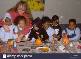 african american kids and mentors painting pumpkins at halloween