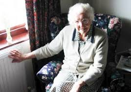 an elderly woman sat in an arm chair with her hand on a radiator.