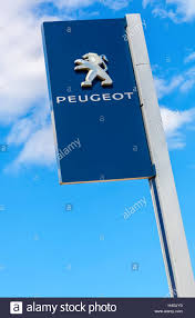 the car peugeot peugeot logo on a sign outside the car or automotive dealership