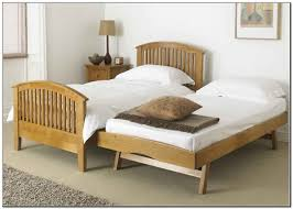 bedroom pop up trundle day bed dark hardwood wall decor lamp
