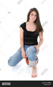 beautiful teen in jeans sitting on ball over white stock