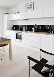 white kitchen cabinets with timber bench black colour back splash