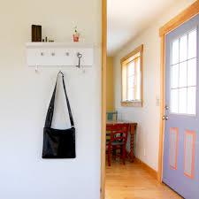 white painted beadboard wall coat rack with narrow top shelf of