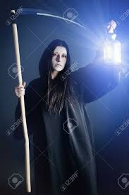 woman death reaper over black background halloween stock photo