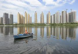 A man rows a boat on a river in front of new properties in Taiyuan  Shanxi province  on July           China     s economy probably will grow at its slowest     The Atlantic