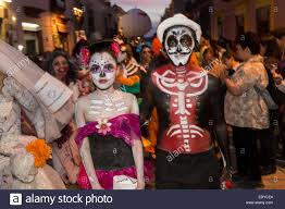 a mexican couple dressed in costumes parades through the streets