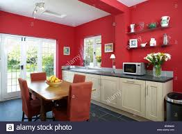 wood table and red upholstered chairs in red kitchen dining room