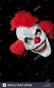 a scary halloween clown mask against a black background stock
