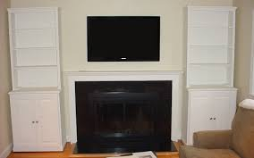 furniture wall mounted tv over fireplace between two tall white