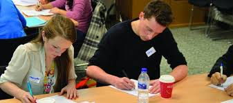Two students sitting at a table writing on sheets of paper