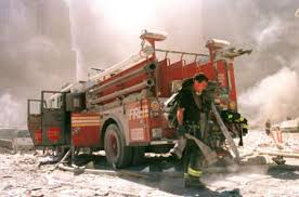 Fire Truck covered with dust at Ground Zero on 9/11 with firemen carrying hose from truck